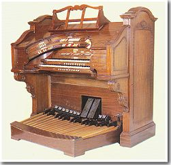 A hot-rod WurliTzer 2-Manual Theatre Pipe Organ console in natural walnut with a double stop tongue bolster.