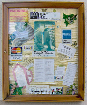 Click here to download a 1192 x 1423 JPG image of a framed collage outside the entrance to Roaring 20's Pizza and Pipes featuring memorabilia from Dwight Thomas.
