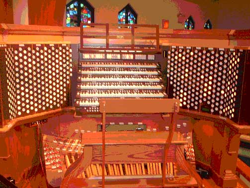 A modern 6-manual draw knob console controlling a huge Church Pipe Organ.