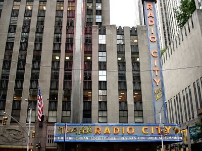 Click here to download a 1280 x 960 JPG image showing the buildings of downtown New York City towering above the Radio City Music Hall marquee.